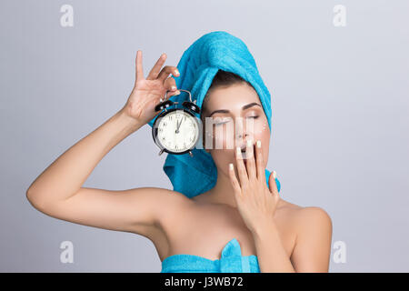Tired yawning woman in towel on head and creme on face holding alarm clock showing midnight, night creme skincare - Stock Photo