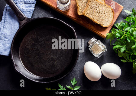Frying pan and eggs. Close up view of ingredients of fried egg and a frying pan. Empty cast iron pan, eggs, salt, - Stock Photo