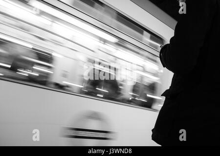 Anonymous passenger stands as District Line train passes at Mile End underground station, east London. - Stock Photo