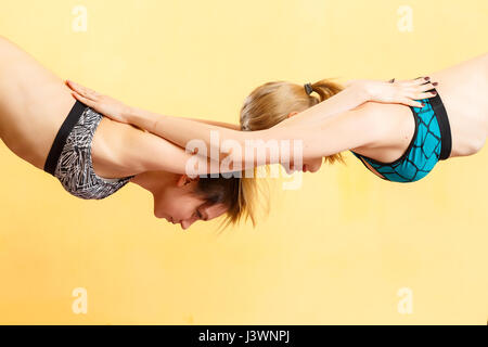 Two young girls doing yoga - Stock Photo
