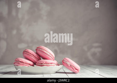 Raspberry pastel pink Macarons or Macaroons on a plate over concrete stone background - Stock Photo