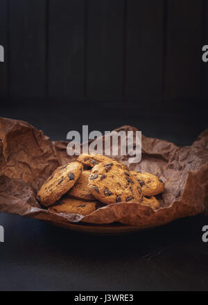 Chocolate chip cookies on crumpled paper over dark background in low light - Stock Photo
