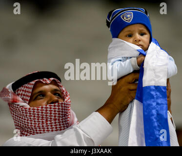 Doha, Qatar. 8th May, 2017. A fan of Al-Hilal holds a baby to celebrate after the AFC Asian Champions League Group - Stock Photo