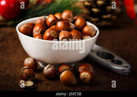 fresh hazelnuts served in a white bowl - Stock Photo