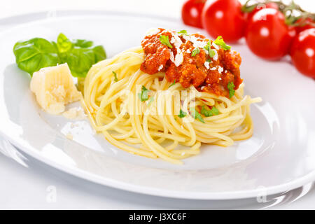 Pasta with meat sauce. Served with parmesan, and basil - Stock Photo
