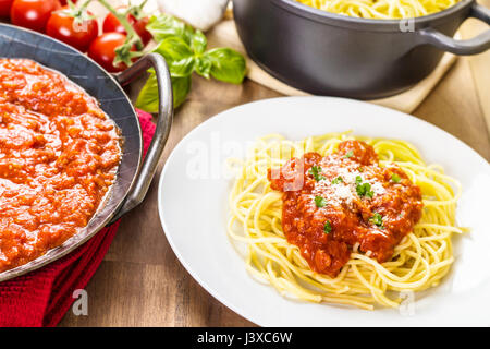 Pasta with meat sauce. Served in a pan. With tomatoes, basil and garlic in the background - Stock Photo
