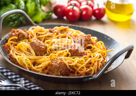 Pasta with meatballs and meat sauce. Served in a pan. with tomatoes, basil and garlic in the background - Stock Photo