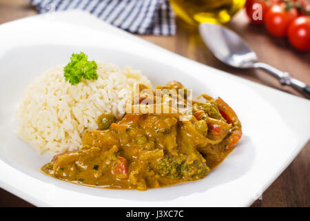 Yellow hot curry dish with mixed vegetables served in a white plate. - Stock Photo