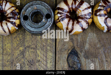 Retro donut cutter with sugar frosted donuts close up on rustic wood table - Stock Photo