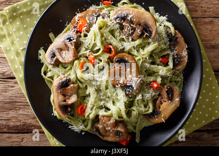 Spinach noodles with mushrooms and parmesan cheese close-up on a plate. Horizontal view from above - Stock Photo