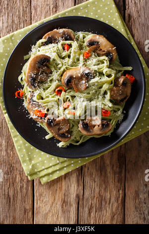 Green spinach pasta with mushrooms and parmesan cheese close-up on a plate. Vertical view from above - Stock Photo