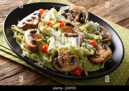 Delicious spinach pasta with fried mushrooms, pepper and parmesan cheese close-up on a plate. horizontal - Stock Photo