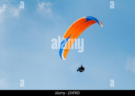 LAKE DISTRICT, UNITED KINGDOM - MAY 22, 2010: A paraglider is flying against a blue sky enjoying the wonderful day - Stock Photo