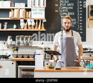 Portrait of a young man behind a counter in a cafe - Stock Photo