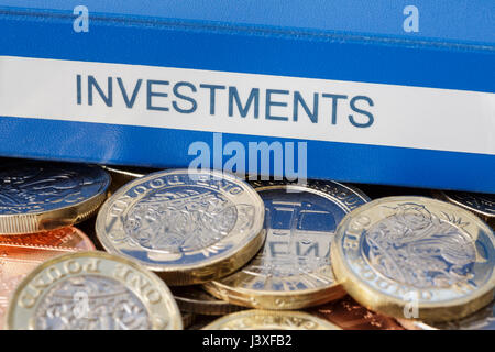 Investments portfolio on English pounds £ sterling money new pound coins GBP cash to illustrate investing and saving - Stock Photo
