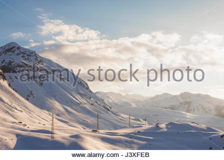 Golden hour of snowy mountains near the Julier pass in the Swiss Alps with electrical pylons on the mountains. - Stock Photo
