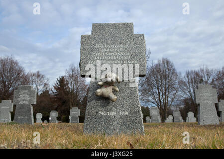 Toy dog fixed to the grave of two unknown children who died during World War II on the ground of the German War - Stock Photo