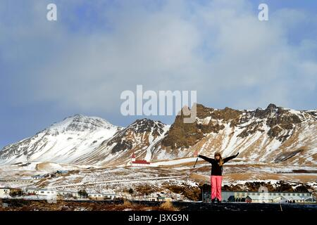 A woman arms stretched enjoys the panorama in Vic Iceland - Stock Photo