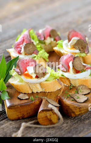 Canapes with roast beef, black autumn truffles, French brie cheese on a slice of egg on baguette with a leaf of - Stock Photo