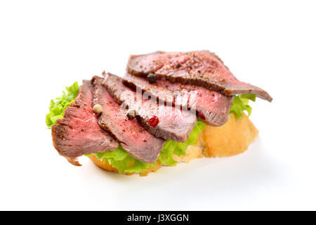Roasted beef fillet with pepper on a slice of baguette with a leaf of salad - Stock Photo