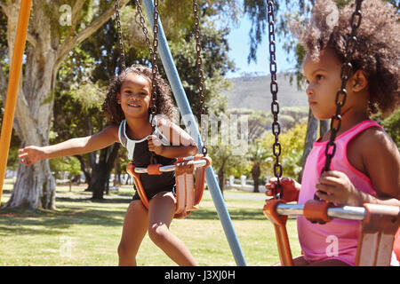 Two young sisters playing on park swings - Stock Photo