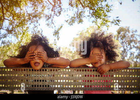 Portrait of two young sisters leaning against fence, covering eyes - Stock Photo