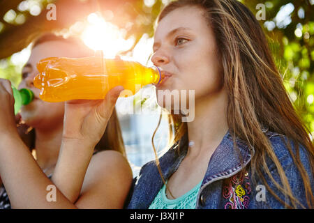 Two female friends sitting outdoors, drinking soft drinks - Stock Photo