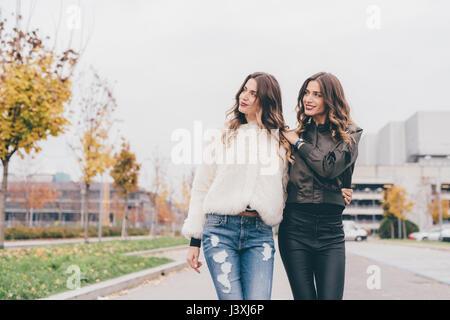 Twin sisters walking outdoors, looking away - Stock Photo