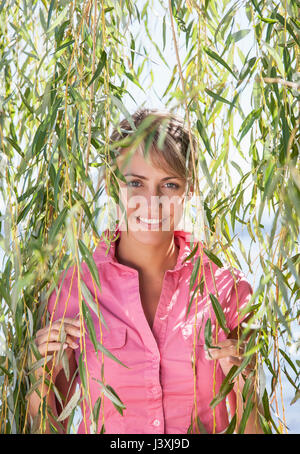 Portrait of woman smiling among weeping willow branches, Lake Maggiore, Italy - Stock Photo