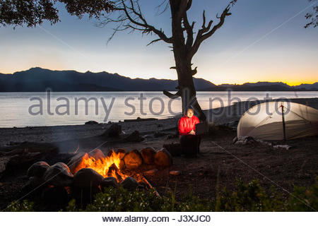 Woman looking at her laptop by a campfire at Nahuel Huapi Lake in Patagonia - Stock Photo