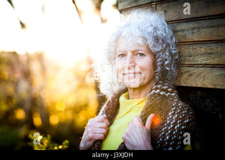 Portrait of mature woman with grey hair leaning against woodland treehouse at sunset - Stock Photo