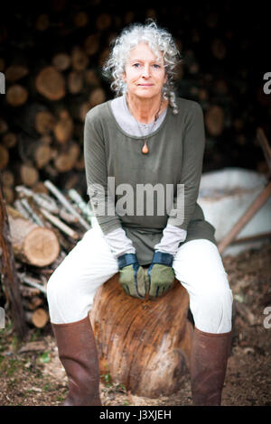 Portrait of mature grey haired woman sitting on log in garden - Stock Photo