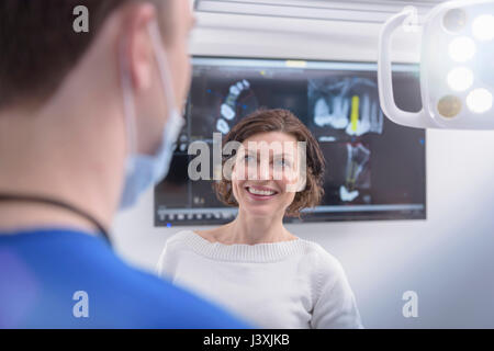 Dentist showing x-rays on screen to patient in dental surgery - Stock Photo