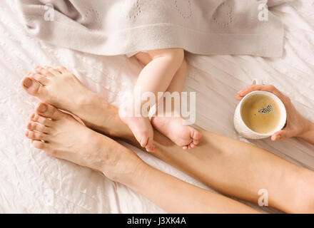Mother and baby's bare feet on each other on bed - Stock Photo