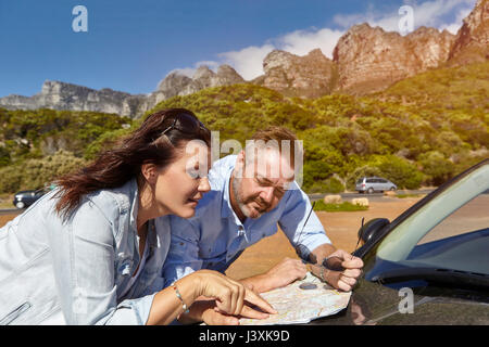 Couple leaning on car bonnet, looking at map, Cape town - Stock Photo