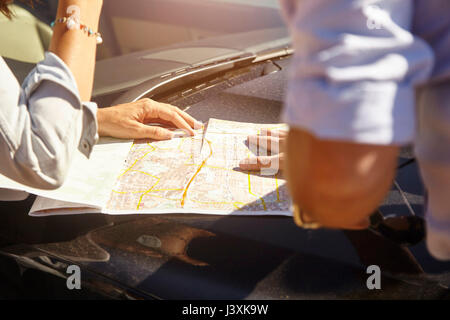 Couple looking at map on car bonnet, mid section - Stock Photo