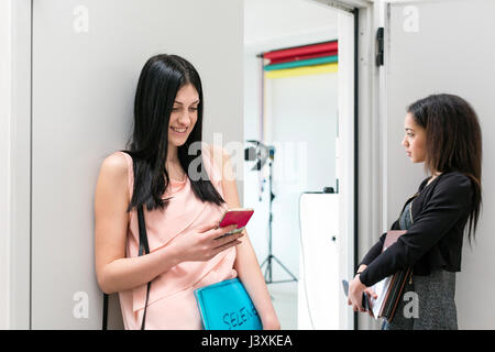 Two fashion models waiting by door of photographic studio - Stock Photo