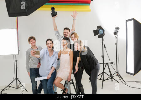 Stylists, model and photographer taking smartphone selfie in photography studio - Stock Photo