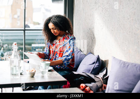 Mid adult woman using digital tablet in cafe - Stock Photo