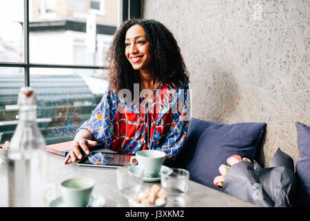 Mid adult woman on cafe window seat - Stock Photo