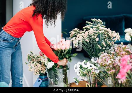 Female florist arranging roses in vase for shop display - Stock Photo