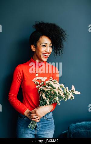 Portrait of happy florist holding cut flowers - Stock Photo