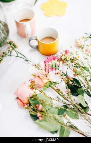 Table with cut flowers and coffee cups at flower arranging workshop - Stock Photo