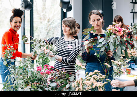 Florist students selecting cut flowers at flower arranging workshop - Stock Photo