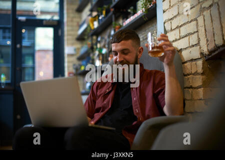 Young man with tumbler of spirit looking at laptop in public house - Stock Photo