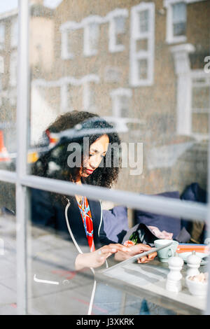 Window view of woman using digital tablet in cafe