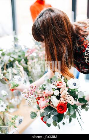 Florist student selecting cut flowers at flower arranging workshop - Stock Photo