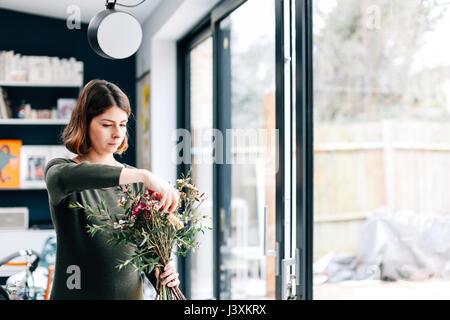 Florist student arranging bouquet at flower arranging workshop - Stock Photo
