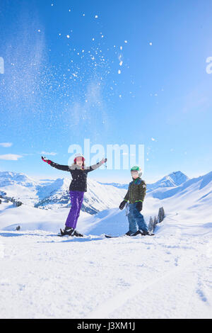 Portrait of skiing teenage girl and brother throwing powder snow in Swiss Alps, Gstaad, Switzerland - Stock Photo