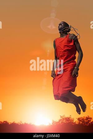 Masai man jumping while performing a Masai traditional dance, Masai Mara National Reserve, Kenya - Stock Photo